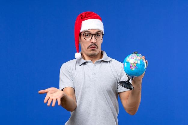 Vista frontal macho joven sosteniendo globo terráqueo sobre pared azul viaje masculino de vacaciones en avión