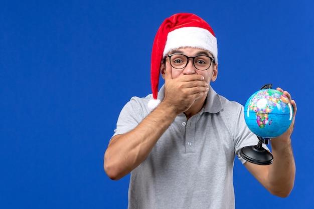 Vista frontal macho joven sosteniendo globo terráqueo sobre una pared azul viajes de vacaciones de aviones humanos