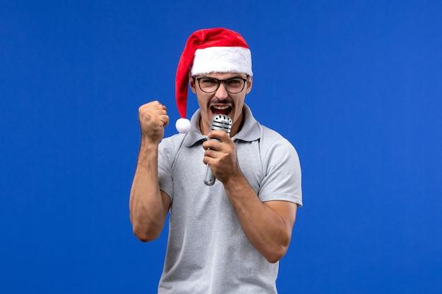 Vista frontal macho joven sosteniendo el micrófono en el escritorio azul año nuevo cantante música masculina