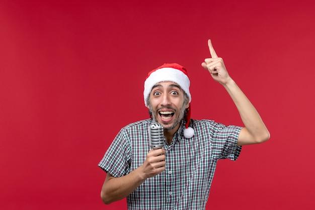 Vista frontal macho joven sosteniendo el micrófono en el escritorio rojo