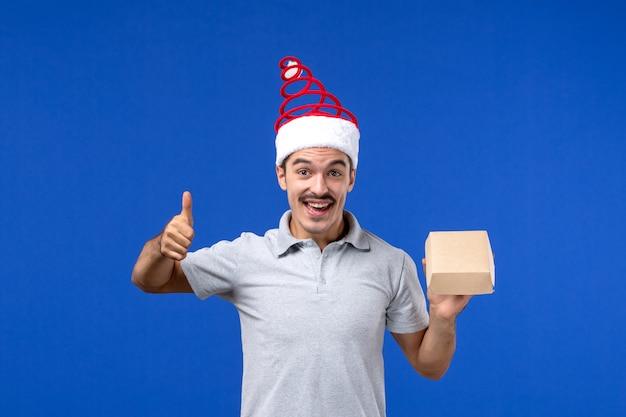 Vista frontal macho joven sosteniendo el paquete de alimentos en la pared azul claro trabajo de servicio masculino de alimentos