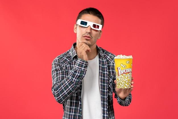 Vista frontal macho joven sosteniendo el paquete de palomitas de maíz en -d gafas de sol pensando en la pared de color rojo claro cine cine cine película