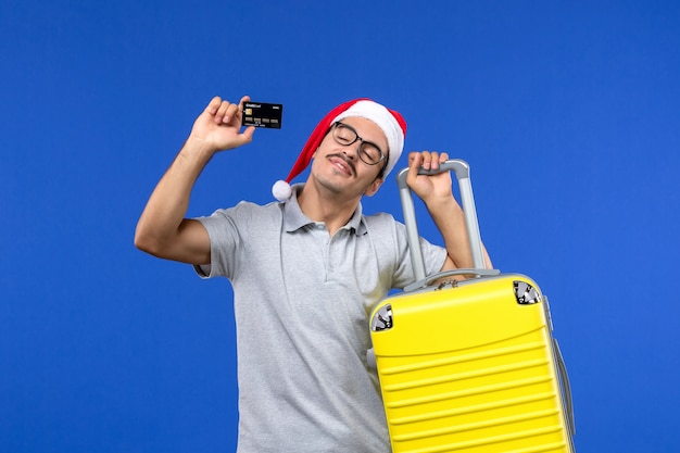Vista frontal macho joven sosteniendo una tarjeta bancaria bolsa amarilla en la pared azul vuelo de avión de vacaciones