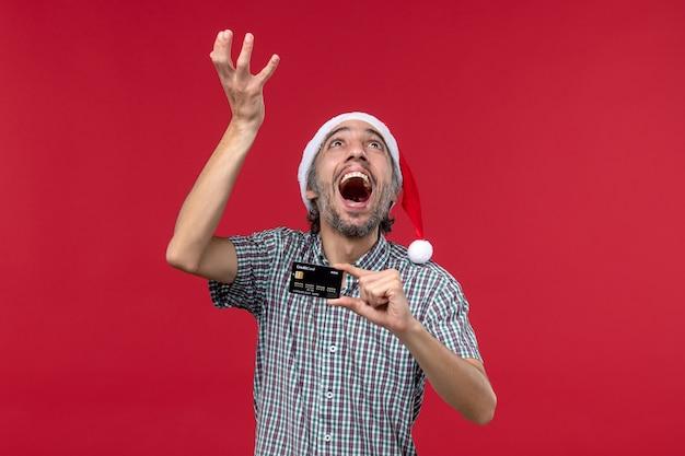 Vista frontal macho joven sosteniendo una tarjeta bancaria sobre fondo rojo.