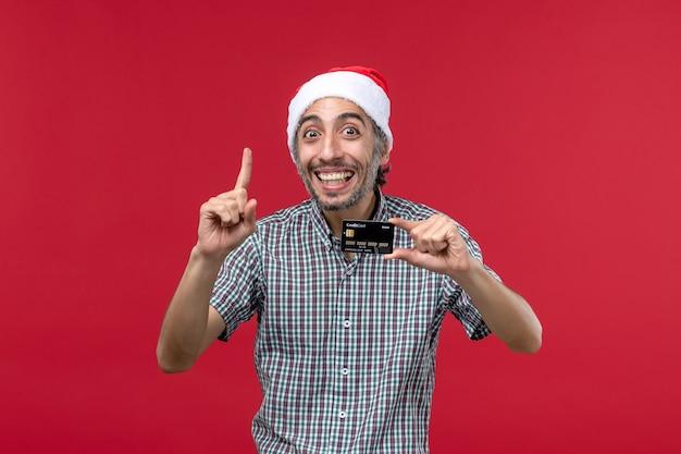 Vista frontal macho joven sosteniendo una tarjeta bancaria con una sonrisa sobre fondo rojo.