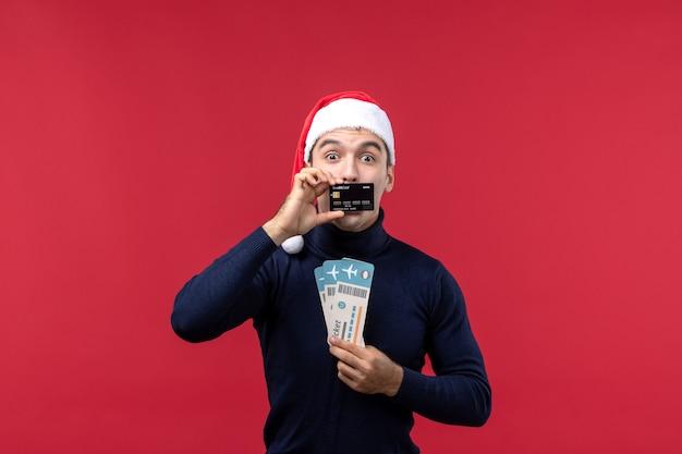 Vista frontal macho joven con tarjeta bancaria y billetes sobre fondo rojo.