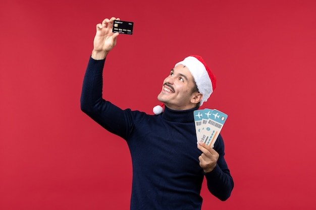 Vista frontal macho joven con tarjeta bancaria de billetes sobre fondo rojo.