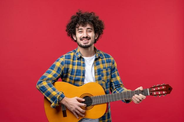 Vista frontal macho joven tocando la guitarra en la pared roja banda de color en vivo aplausos música tocar músico