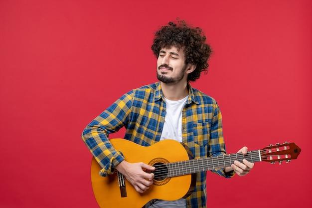 Vista frontal macho joven tocando la guitarra en la pared roja, concierto en vivo, banda de color, aplauso, músico de música