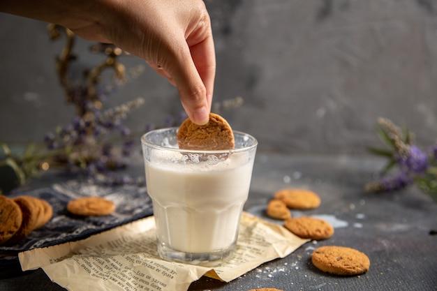 Una vista frontal macho mojar la galleta en el vaso de leche con flores de color púrpura sobre la mesa gris galleta de té de galleta dulce