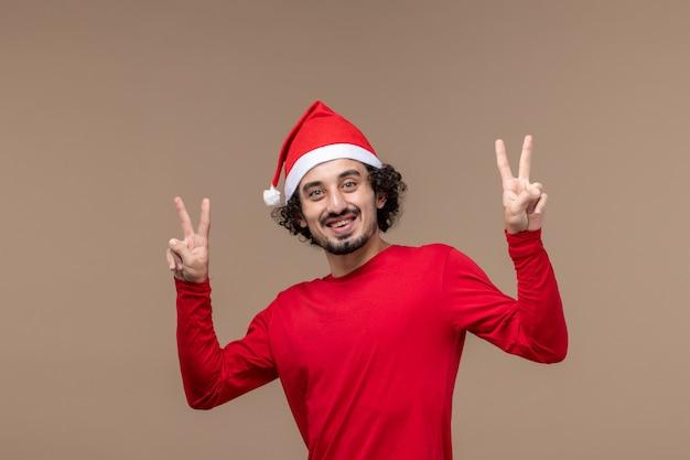 Vista frontal macho en rojo con cara sonriente sobre fondo marrón vacaciones emoción navidad