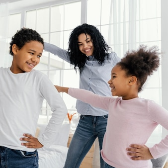 Vista frontal de la madre bailando en casa con sus hijos