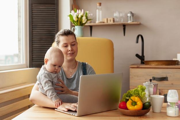 Vista frontal madre con bebé en casa
