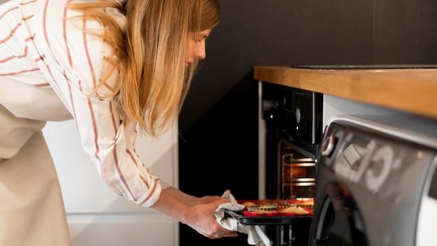 Vista frontal de la madre cocinando en casa