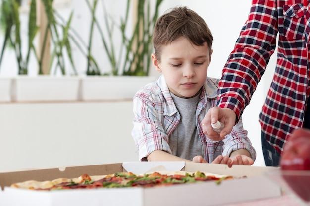 Vista frontal de la madre desinfectando las manos del hijo antes de comer pizza