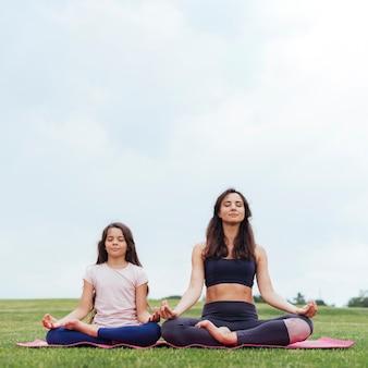 Vista frontal madre e hija meditando al aire libre