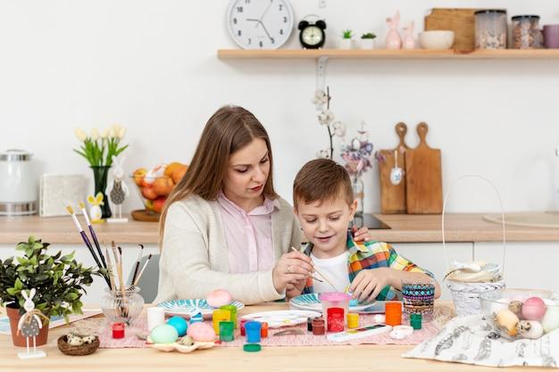 Vista frontal madre e hijo en casa pintando huevos
