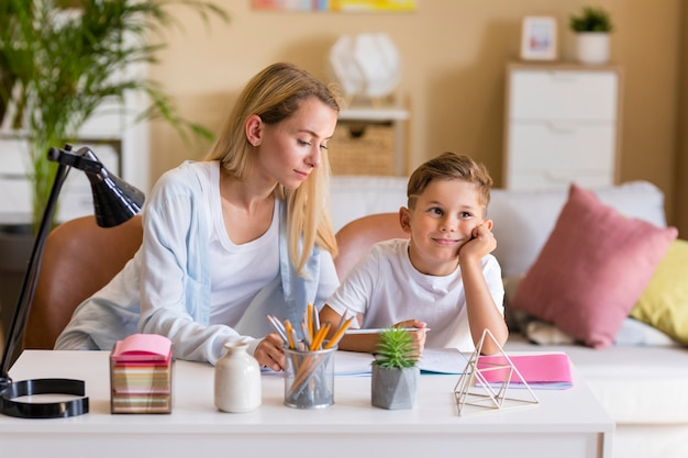 Vista frontal madre e hijo haciendo la tarea en el interior