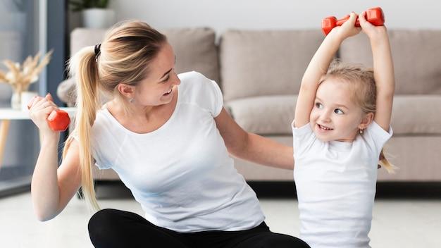 Vista frontal de la madre y la hija haciendo ejercicio con pesas en casa