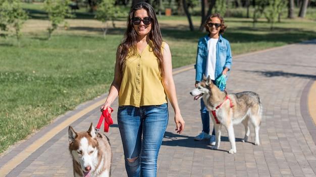 Vista frontal de la madre y el hijo paseando a los perros en el parque