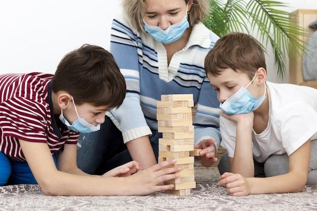 Vista frontal de la madre jugando jenga con niños en casa mientras usa máscaras médicas