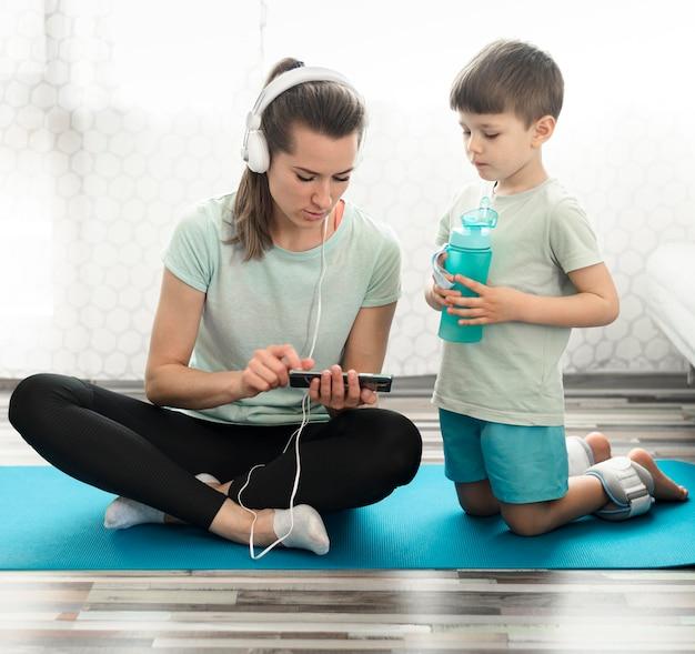 Vista frontal madre junto con hijo en estera de yoga
