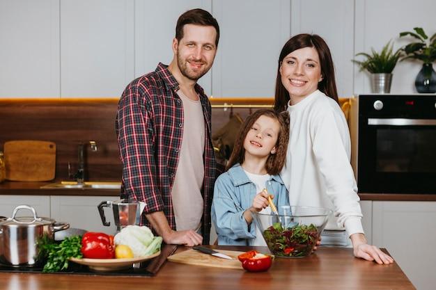 Vista frontal de la madre y el padre con la hija posando en la cocina
