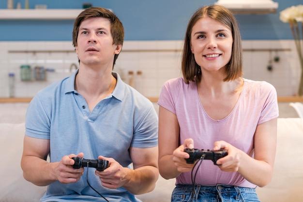 Vista frontal de la madre y el padre jugando videojuegos