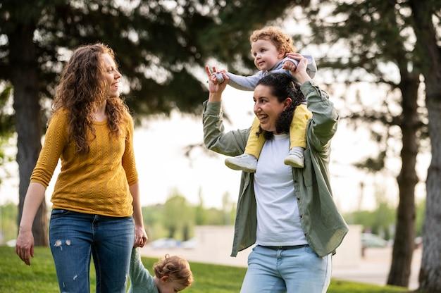 Vista frontal de madres lgbt felices afuera en el parque con sus hijos