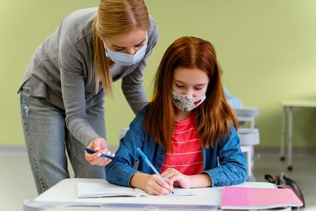 Vista frontal de la maestra con máscara médica ayudando a la niña en clase