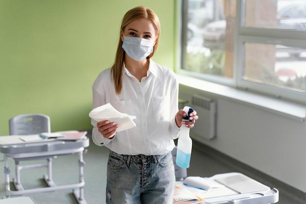 Vista frontal de la maestra con solución desinfectante en el aula