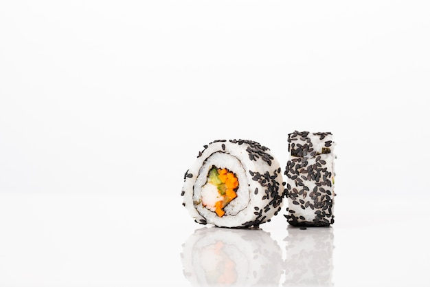 Vista frontal maki sushi rolls con semillas de sésamo negro