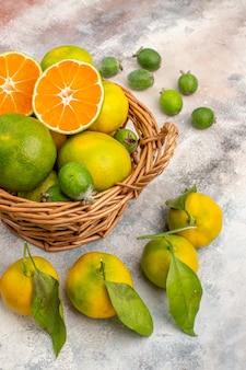 Vista frontal mandarinas frescas en cesta de mimbre rodeada de mandarinas feijoas sobre fondo desnudo