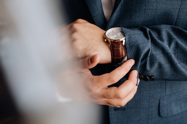 Vista frontal de una manga del traje de hombre y manos con elegante reloj