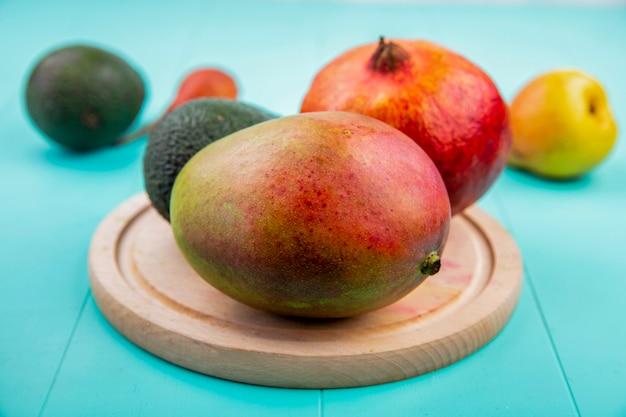 Vista frontal de mango con granada sobre una tabla de cocina de madera sobre superficie azul