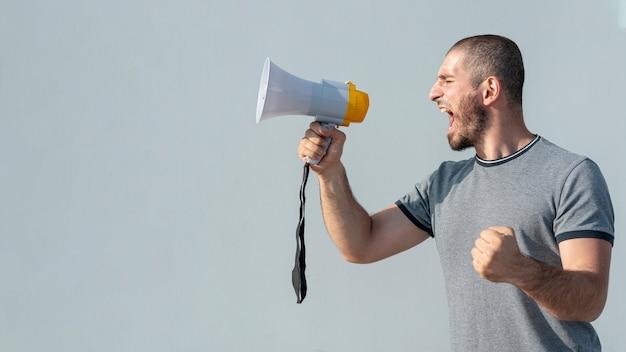Vista frontal manifestante con megáfono gritando