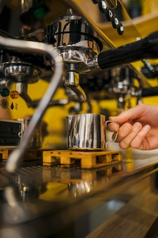 Vista frontal de la mano del barista en la máquina de café