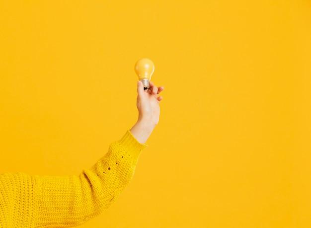 Vista frontal mano con bombilla amarilla