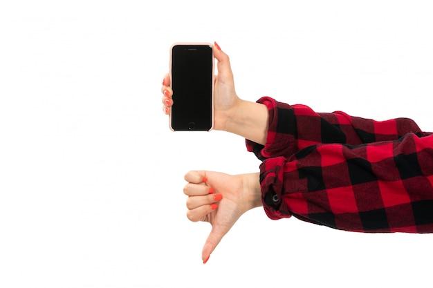 Una vista frontal mano femenina en camisa a cuadros negro-rojo con teléfono inteligente que muestra signo no genial en el blanco