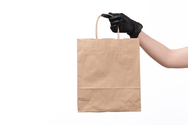 Una vista frontal mano femenina en guante negro con paquete de alimentos de papel en blanco