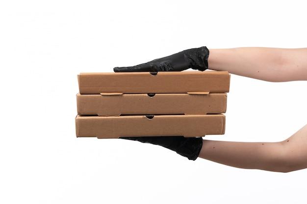 Una vista frontal mano femenina en guantes negros con cajas de pizza en blanco
