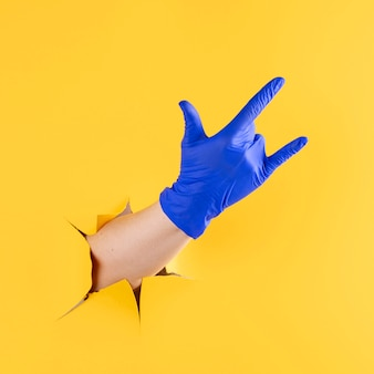 Vista frontal de la mano con guante quirúrgico mostrando gesto de rock and roll