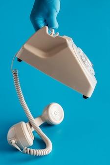 Vista frontal de la mano con guante sosteniendo teléfono