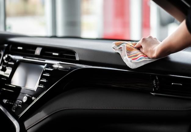 Vista frontal de la mano limpiando el interior del automóvil