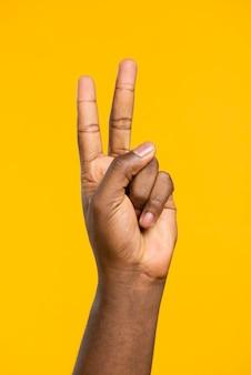 Vista frontal mano mostrando el signo de paz