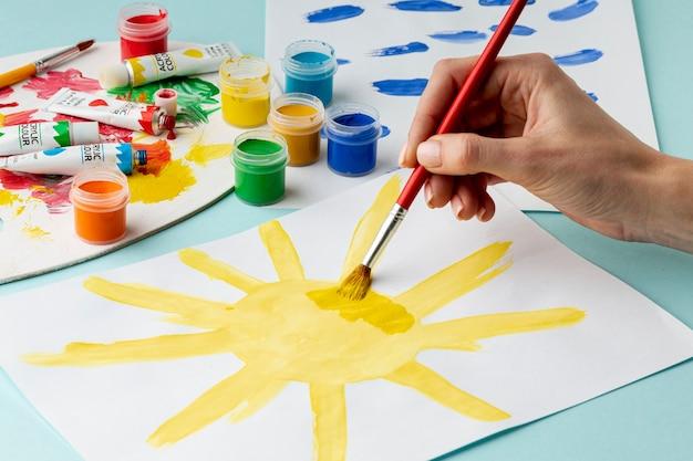 Vista frontal de la mano pintando un sol