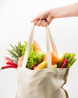 Vista frontal de la mano que sostiene la bolsa reutilizable con frutas y verduras