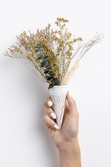Vista frontal de la mano que sostiene el cono de helado con flores