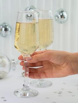 Vista frontal de la mano que sostiene la copa de champán