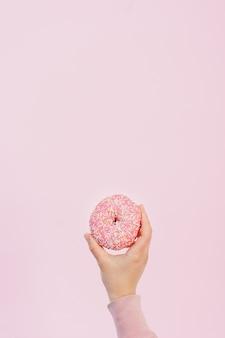 Vista frontal de la mano que sostiene donut glaseado con chispas y espacio de copia